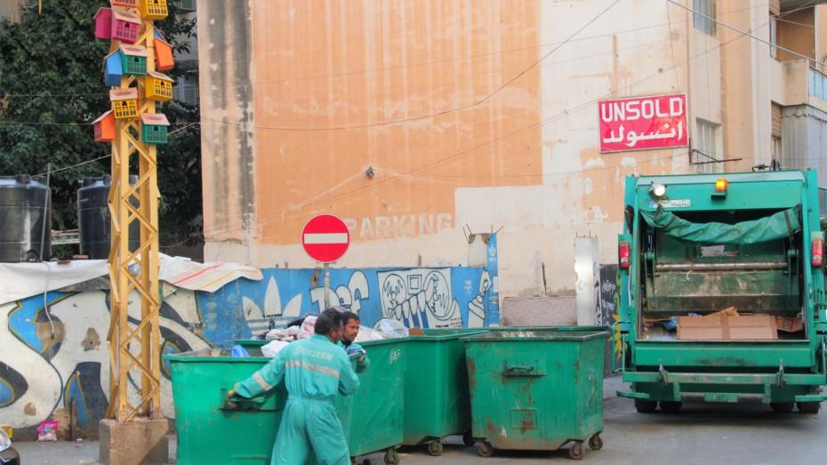Garbage men taking out trash at birdhouses