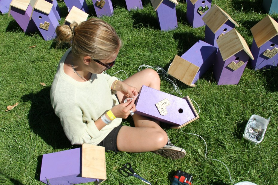 girl attaches hearts to recycled birdhouses