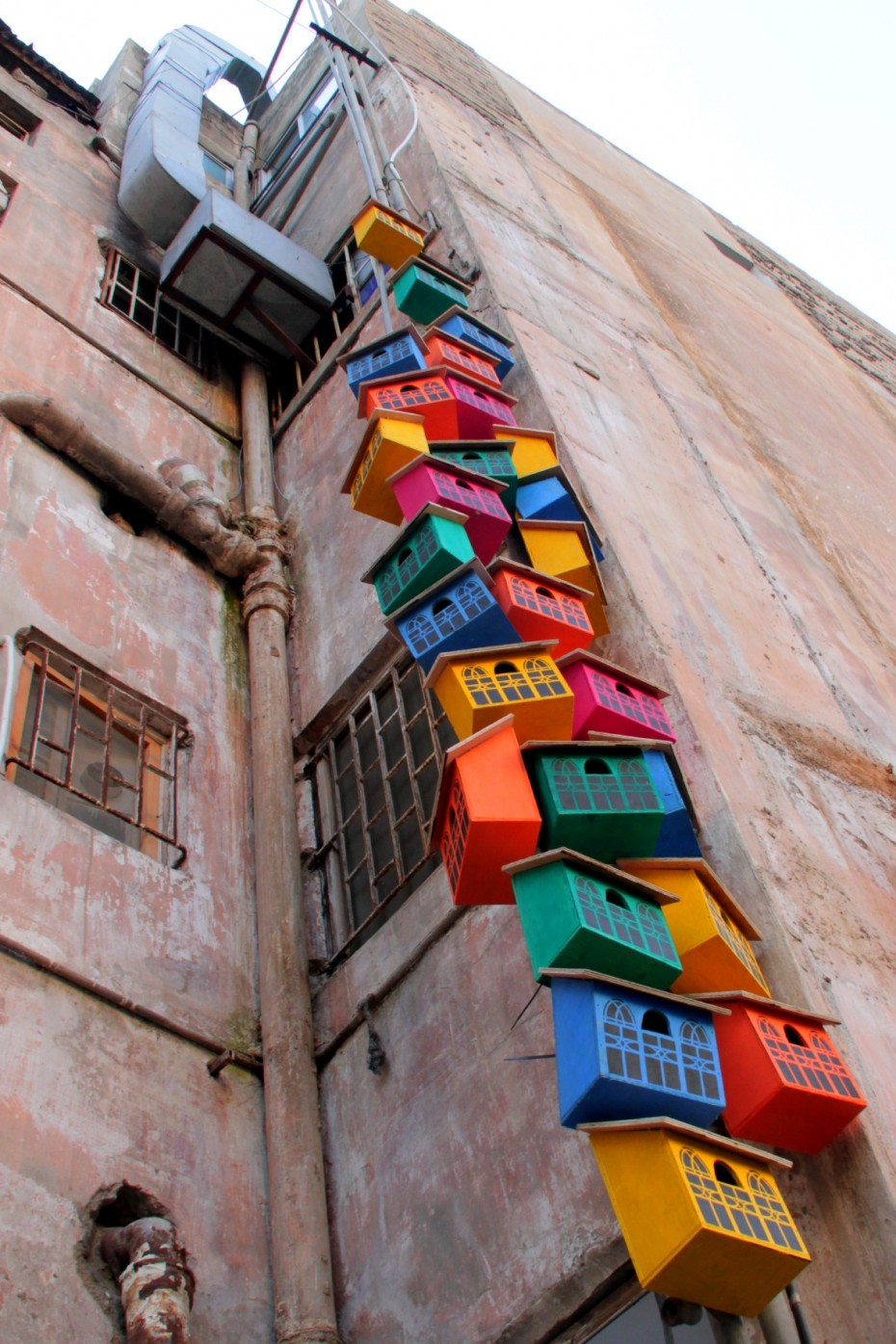 Upcycled birdhouses on a mural in Beirut
