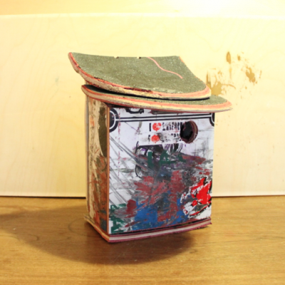 Squared bird house made from broken skateboards